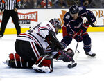 Chicago Blackhawks goalie Corey Crawford, left, stops a shot by Columbus Blue Jackets forward Cam Atkinson during the second period of an NHL hockey game in Columbus, Ohio, Saturday, Oct. 20, 2018. (AP Photo/Paul Vernon)