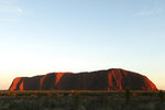 FILE - In this April 22, 2014, file photo, the sun rises over Uluru, Australia. A climbing ban from late Friday, Oct. 25, 2019 on the sandstone monolith called Uluru that dominates Australia's arid center marks indigenous Australians finding a new voice in national decision-making. The rock has long been celebrated as a prized peak to conquer and a sacred site to be revered, but with the ban, the pendulum is swinging decisively toward the rock's cultural significance to its traditional owners. (AP Photo/Rob Griffith, File)