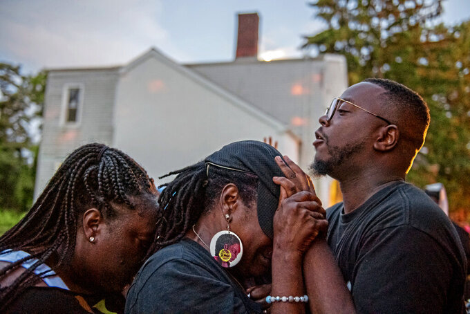 From left, Brittny Jackson embraces Terry Green who receives a blessing from Rev. Michael Day at the end of a worship service on Wednesday, Aug. 18, 2021, in Northview Heights in Pittsburgh.  Day is making it his mission to work with the city and group violence outreach workers to address the needs of families in Northview Heights. He and church members planned to set up a tent in the neighborhood and try to connect residents to counseling, basic necessities and church ministries.(Ben Braun/Pittsburgh Post-Gazette via AP)
