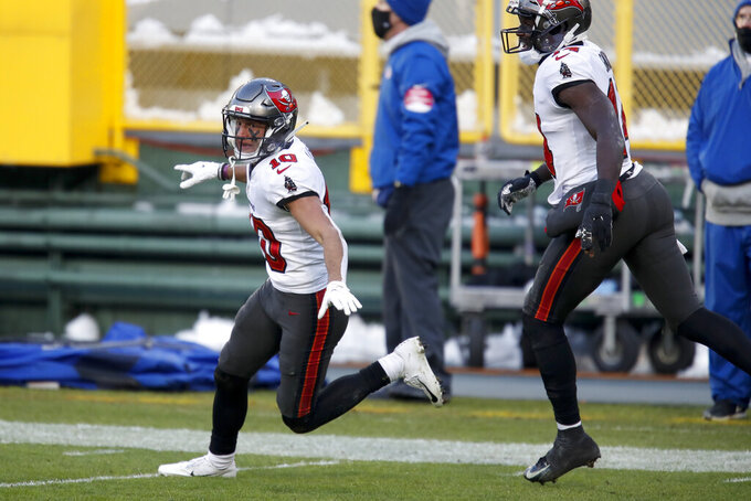 Tampa Bay Buccaneers' Scott Miller, left, celebrates after catching a 39-yard touchdown pass against the Green Bay Packers during the first half of the NFC championship NFL football game in Green Bay, Wis., Sunday, Jan. 24, 2021. (AP Photo/Matt Ludtke)