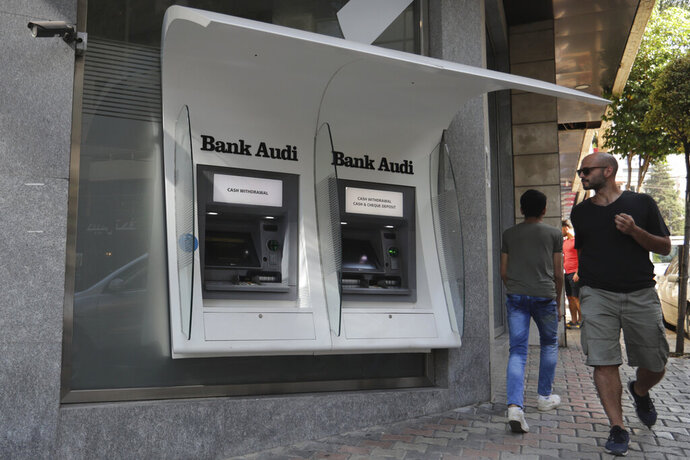FILE - In this Tuesday, Nov. 12, 2019 file photo, people pass by an out of service ATM machines at a closed bank in the Lebanese capital Beirut. Lebanon's bank staff union announced Monday, Nov. 18, 2019 that it's ending a week-long strike after increased security and new regulations that make limits on withdrawal and dollar transfers official. The union said that banks will reopen Tuesday. (AP Photo/Hassan Ammar, File)