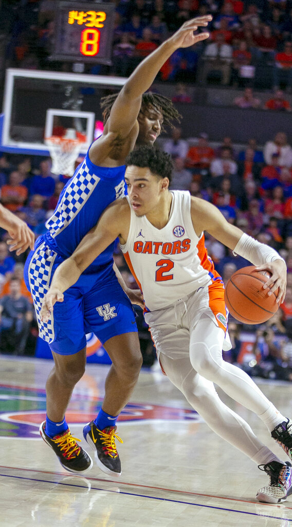 Florida guard Andrew Nembhard (2) powers past Kentucky guard Tyrese Maxey (3) during the first half of an NCAA college basketball game Saturday, March 7, 2020, in Gainesville, Fla. (AP Photo/Alan Youngblood)