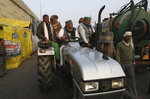 Indian Farmers arrive in a tractor for their tractor rally planned for Jan. 26 in protest against new farm laws, at Delhi-Uttar Pradesh border, India, Friday, Jan. 22, 2021. Talks between protesting farmers' leaders and the government ended abruptly in a stalemate on Friday with the agriculture minister saying he has nothing more to offer than suspending contentious agricultural laws for 18 months. The farmers' organizations in a statement on Thursday said they can't accept anything except the repeal of the three new laws. (AP Photo/Manish Swarup)