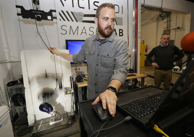 In this photo taken May 23, 2019, Ryan Smith, a test engineer at VICIS, a Seattle-based company that makes football helmets, runs a head-to-helmet impact test in a testing lab in Seattle. The company's latest offering is the ULTIM cap, which is intended for use with youth flag football and competitive 7-on-7 football played during the offseason for youth and high school programs. (AP Photo/Ted S. Warren)