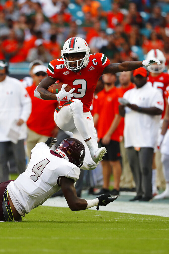Miami wide receiver Mike Harley (3) attempts to avoid Bethune-Cookman cornerback De'Ron Maxwell (4) during the first half of an NCAA college football game Saturday, Sept. 14, 2019, in Miami Gardens, Fla. (AP Photo/Wilfredo Lee)