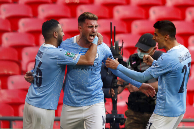 Manchester City's Aymeric Laporte, center, celebrates with Riyad Mahrez, left, and Joao Cancelo after scoring the opening goal during the English League Cup final soccer match between Manchester City and Tottenham Hotspur at Wembley stadium in London, Sunday, April 25, 2021. (AP Photo/Alastair Grant)