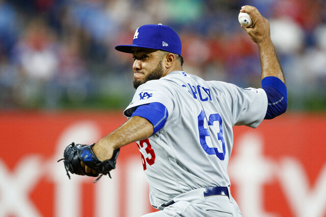 FILE- In this  July 15, 2019, file photo, Los Angeles Dodgers' Yimi Garcia pitches during a baseball game against the Philadelphia Phillies in Philadelphia. Garcia, who pitched in 64 games this year for the Dodgers, has signed a one-year contract with the Miami Marlins. (AP Photo/Matt Slocum, File)
