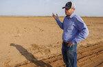 Will Thelander, a fourth-generation farmer, talks about having to leave fields unplanted as less water from the Colorado River makes it to his farm in Casa Grande, Ariz., Thursday July 22, 2021. The Colorado River has been a go-to source of water for cities, tribes and farmers in the U.S. West for decades. But climate change, drought and increased demand are taking a toll. The U.S. Bureau of Reclamation is expected to declare the first-ever mandatory cuts from the river for 2022. (AP Photo/Darryl Webb)