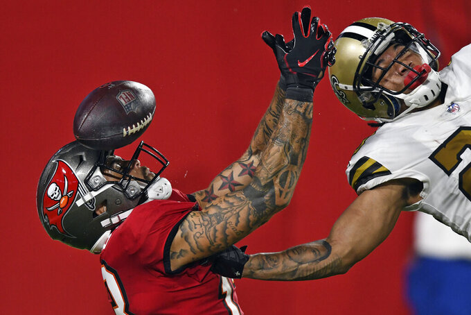 New Orleans Saints cornerback Marshon Lattimore, right, knocks the ball away from Tampa Bay Buccaneers wide receiver Mike Evans in the endzone on a fourth down during the second half of an NFL football game in Tampa, Fla., on Nov. 8, 2020. (AP Photo/Jason Behnken)