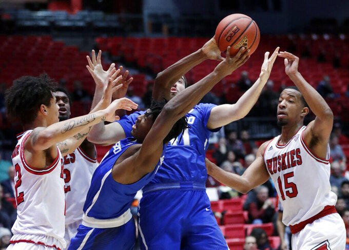 Buffalo forward Jeenathan Williams, second from left, tries to controls the ball against Northern Illinois guard Rod Henry-Hayes, left, and forward Jaylen Key, right, during the first half of an NCAA college basketball game Tuesday, Jan. 22, 2019, in DeKalb, Ill. (AP Photo/Nam Y. Huh)