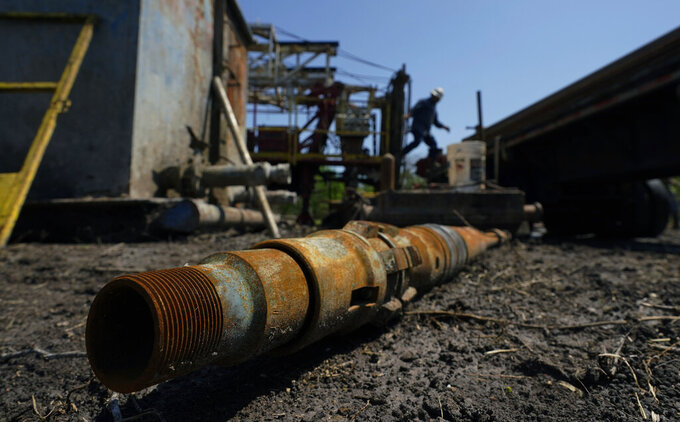 An oil well worker moves equipment at a site on the Rooke family ranch where an orphaned well was plugged, Tuesday, May 18, 2021, near Refugio, Texas. There are 3.2 million abandoned oil and gas wells in the U.S., according to the Environmental Protection Agency. About a third were plugged with cement, which is considered the proper way to prevent harmful chemical leaks. But most, about 2.1 million by the EPA's count, haven't been plugged at all. (AP Photo/Eric Gay)