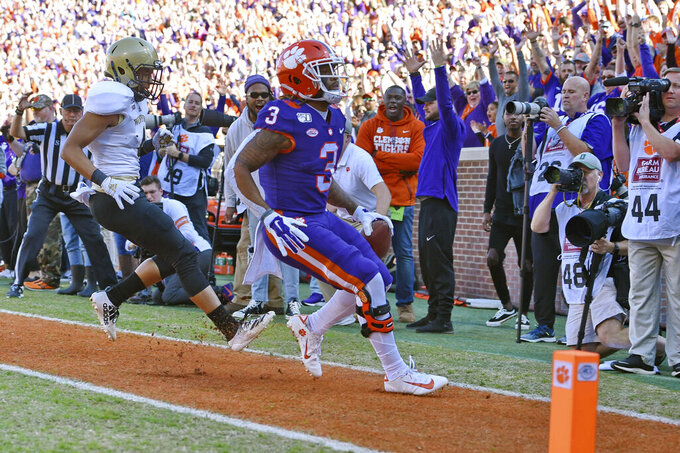 Clemson's Amari Rodgers (3) scores a touchdown while defended by Wofford's Keyvaun Cobb during the first half of an NCAA college football game, Saturday, Nov. 2, 2019, in Clemson, S.C. (AP Photo/Richard Shiro)