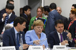 German Chancellor Angela Merkel, center, flanked by Canadian Prime Minister Justin Trudeau, left, and Italian Prime Minister Giuseppe Conte, right, talk before the start of the G-20 summit event on the Digital Economy in Osaka, Japan, Friday, June 28, 2019. (AP Photo/Susan Walsh)