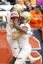 Boston College's Zay Flowers, left, celebrates with teammate Dennis Grosel, right, after scoring a touchdown during the second quarter of an NCAA college football game against Syracuse in Syracuse, N.Y., Saturday, Nov. 2, 2019. (AP Photo/Nick Lisi)