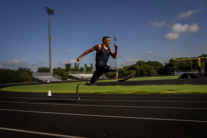 """Luis Puertas runs with his prosthetic blades during one of his daily training sessions in a sports complex in Orlando, Fla., on Monday, Aug. 9, 2021. He's matter of fact about his injuries -- """"In the Paralympics everybody has a story. There's always some guy whose story is worse."""" But the first years were rough. (AP Photo/Emilio Morenatti)"""