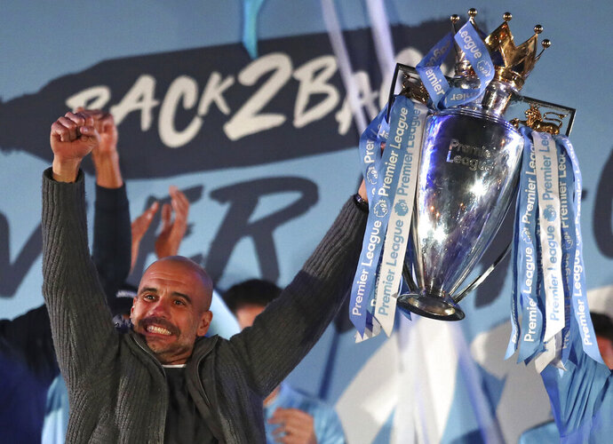 Manchester City coach Pep Guardiola holds the trophy as he celebrates with supporters at the Etihad Stadium in Manchester, England, Sunday May 12, 2019 the day they won the English Premier League title. Manchester City retained the Premier League trophy after coming from behind to beat Brighton 4-1 and see off Liverpool's relentless challenge on the final day of the season on Sunday. (AP Photo/Jon Super)