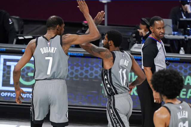 Brooklyn Nets forward Kevin Durant (7) celebrates with guard Kyrie Irving (11) during a timeout in the fourth quarter of the team's NBA basketball game against the Atlanta Hawks, Wednesday, Dec. 30, 2020, in New York. The Nets won 145-141. (AP Photo/Kathy Willens)