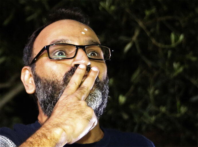 Ziad Itani, a Lebanese stage actor who was indicted on charges of collaborating with Israel and drug possession, sends kisses to his supporters after he was released by Lebanese authorities, at his house, in Beirut, Lebanon, Tuesday, March 13, 2018. Itani was released on Tuesday and cleared of charges, while the officer who built the case against him was ordered detained.(AP Photo/Hussein Malla)
