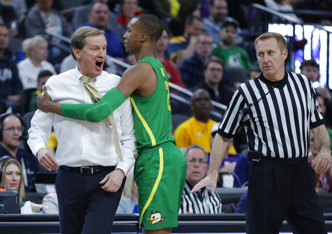 Oregon's Louis King, center, pulls head coach Dana Altman away from an official during the second half of an NCAA college basketball game in the semifinals of the Pac-12 men's tournament Friday, March 15, 2019, in Las Vegas. (AP Photo/John Locher)