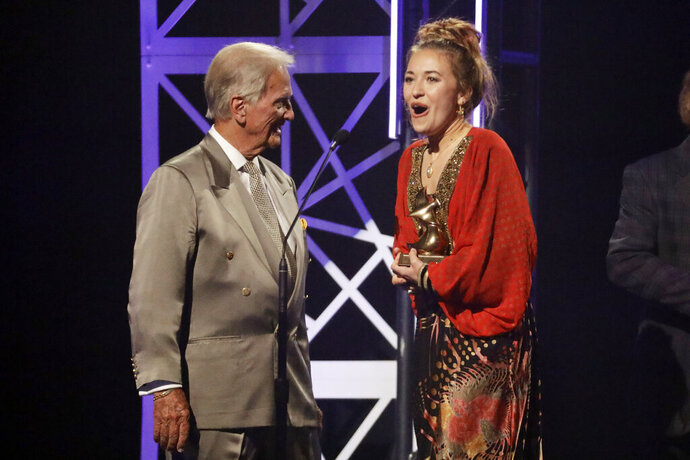 Lauren Daigle, right, accepts the song of the year award from Pat Boone, left, during the Dove Awards on Tuesday, Oct. 15, 2019, in Nashville, Tenn. (AP Photo/Mark Humphrey)
