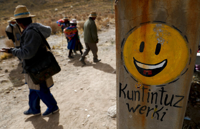 """Residents walk past a cement post decorated with a smiley face and a message that reads in Uru; """"I'm happy,"""" in the Urus del Lago Poopo indigenous community, in Punaca, Bolivia, Monday, May 24, 2021. None of the inhabitants speak Uru, the language of their ancestors. However, in the past few years they have decided to recover their native language. (AP Photo/Juan Karita)"""