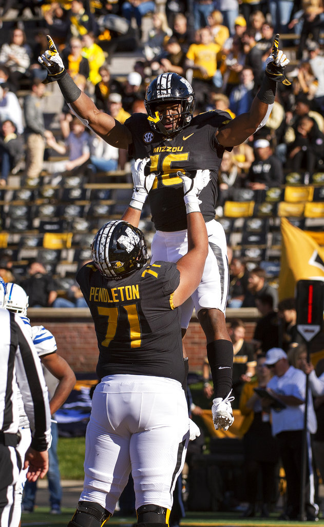 Missouri running back Damarea Crockett, top, celebrates his touchdown with teammate Kevin Pendleton, bottom, during the first half of an NCAA college football game Saturday, Oct. 20, 2018, in Columbia, Mo. (AP Photo/L.G. Patterson)