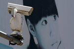 A video surveillance camera made by China's Hikvision is mounted on top of a street near a advertisement poster in Beijing, Thursday, May 23, 2019.  The video surveillance company says it is taking concern about the use of its technology seriously following a report that the U.S. may block several Chinese surveillance companies from buying American components. (AP Photo/Andy Wong)