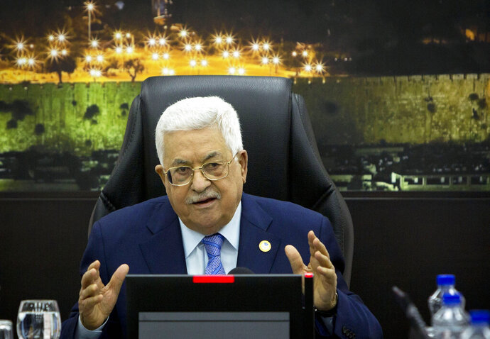 FILE - In this April 29, 2019, file photo, Palestinian President Mahmoud Abbas, center, chairs a session of the weekly cabinet meeting in the West Bank city of Ramallah. The Trump administration will unveil the first phase of its long-awaited blueprint for Mideast peace next month at a conference in the region designed to highlight economic benefits that could be reaped if the Israeli-Palestinian conflict is resolved, the White House said Sunday, May 19. Jared Kushner and Jason Greenblatt, envoy of international negotiations, have been leading efforts to write the plan, but so far, there's been no participation from the Palestinians. (AP Photo/Majdi Mohammed, Pool, File)