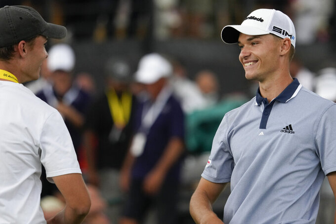Nicolai Hojgaard of Denmark, right, smiles at his twin brother Rasmus after winning the Italian Open golf tournament, in Guidonia, in the outskirts of Rome, Sunday, Sept. 5, 2021. The Italian Open took place on the redesigned Marco Simone course just outside Rome that will host the 2023 Ryder Cup.(AP Photo/Andrew Medichini)
