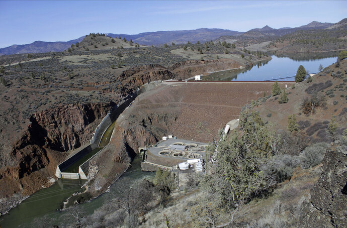 FILE - This March 3, 2020, file photo shows the Iron Gate Dam, powerhouse and spillway are on the lower Klamath River near Hornbrook, Calif. California Gov. Gavin Newsom has appealed directly to investor Warren Buffet to support demolishing four hydroelectric dams on a river along the Oregon-California border to save salmon populations that have dwindled to almost nothing. Newsom on Wednesday, July 28, 2020, wrote Buffet, urging him to back the Klamath River project, which would be the largest dam removal in U.S. history. (AP Photo/Gillian Flaccus, File)