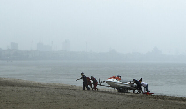 Rescue personnel relocate their jetski as part of precautions against cyclone on the Arabian Sea coast in Mumbai, India, Tuesday, June 2, 2020. Cyclone Nisarga in the Arabian Sea was barreling toward India's business capital Mumbai on Tuesday, threatening to deliver high winds and flooding to an area already struggling with the nation's highest number of coronavirus infections and deaths. (AP Photo/Rajanish Kakade)