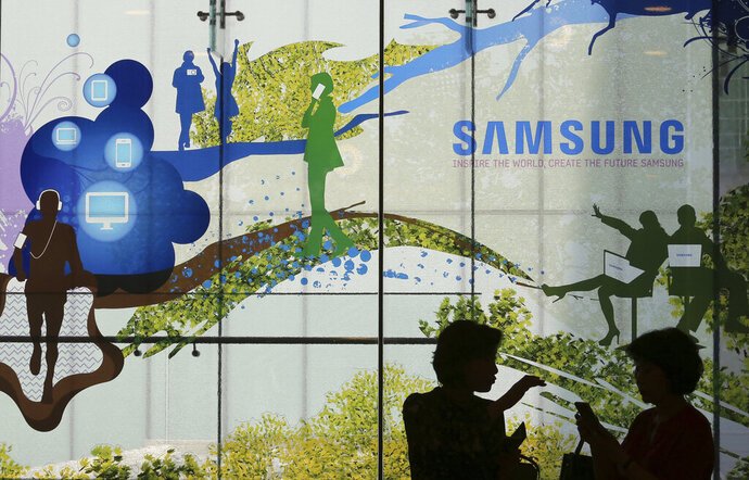 Visitors are silhouetted at Samsung Electronics shop in Seoul, South Korea, Friday, July 5, 2019. Samsung Electronics Co. said Friday its operating profit for the last quarter likely fell more than 56% from a year earlier amid a weak market for memory chips. (AP Photo/Ahn Young-joon)