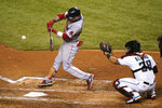 Boston Red Sox's Alex Verdugo, left, hits a single during the third inning of a baseball game against the Miami Marlins, Wednesday, Sept. 16, 2020, in Miami. At right is Miami Marlins catcher Jorge Alfaro. (AP Photo/Lynne Sladky)