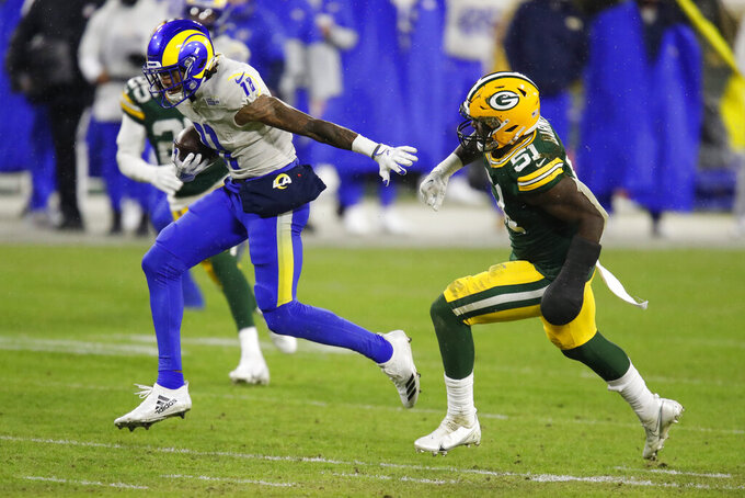 Los Angeles Rams' Josh Reynolds (11) evades a tackle by Green Bay Packers' Krys Barnes (51) during the first half of an NFL divisional playoff football game Saturday, Jan. 16, 2021, in Green Bay, Wis. (AP Photo/Matt Ludtke)