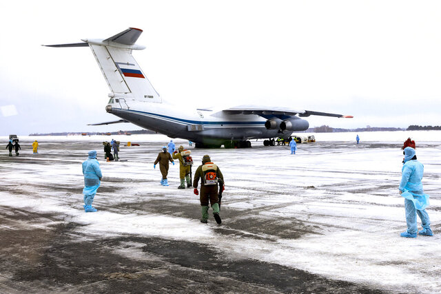A group of medical personnel stands ready to control 80 people, accompanied by medical specialists, carried by a Russian military plane at an airport outside Tyumen, Russia, Wednesday, Feb. 5, 2020. Russia has evacuated 144 people - Russians and nationals of Belarus, Ukraine and Armenia - from the epicenter of the coronavirus outbreak in Wuhan, China, on Wednesday. All evacuees will be quarantined for two weeks in a sanatorium in the Tyumen region in western Siberia, government officials said. (AP Photo/Maxim Slutsky)