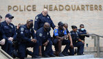 Members of the Austin Police Department kneel in front of demonstrators who gathered in Austin, Texas, Saturday, June 6, 2020, to protest the death of George Floyd, a black man who was in police custody in Minneapolis. Floyd died after being restrained by Minneapolis police officers on Memorial Day. (AP Photo/Eric Gay)