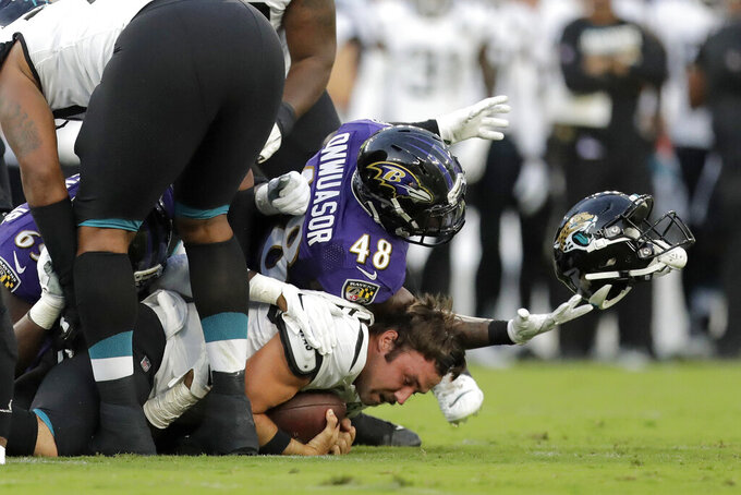Jacksonville Jaguars quarterback Gardner Minshew, bottom, loses his helmet while being sacked by several Baltimore Ravens, including inside linebacker Patrick Onwuasor (48), during the first half of an NFL football preseason game Thursday, Aug. 8, 2019, in Baltimore. (AP Photo/Julio Cortez)
