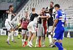Juventus players celebrate at the end of Serie A soccer match between Juventus and Sampdoria at the Allianz stadium, in Turin, Italy, Sunday, July 26, 2020. Juventus clinched a record-extending ninth successive Serie A title, after it defeated Sampdoria 2-0. (AP Photo/Antonio Calanni)
