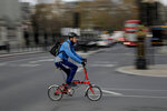 A man cycles on a Brompton folding bicycle in central London, during England's second coronavirus lockdown, Friday, Nov. 20, 2020. The team at Brompton Bicycles company thought they were prepared for Britain's Brexit split with Europe, but they face uncertainty about supplies and unexpected new competition from China, all amid a global COVID pandemic. (AP Photo/Matt Dunham)