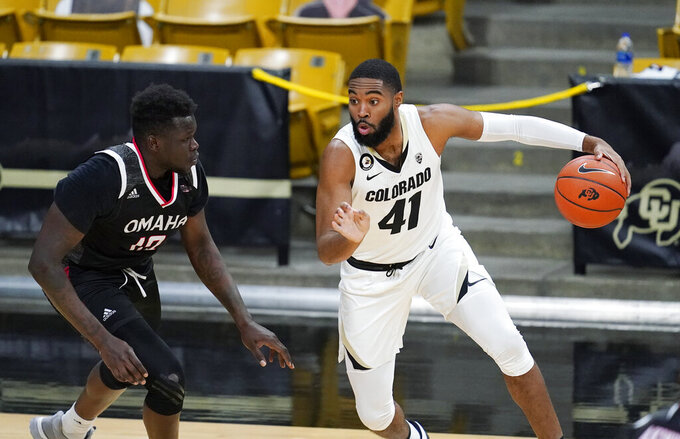 Colorado forward Jeriah Horne, right, drives to the rim past Omaha forward Wanjang Tut in the first half of an NCAA college basketball game Wednesday, Dec. 16, 2020, in Boulder, Colo. (AP Photo/David Zalubowski)
