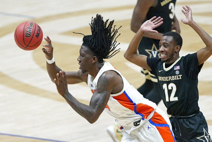 Florida's Anthony Duruji, left, passes the ball as he is defended by Vanderbilt's Trey Thomas (12) in the second half of an NCAA college basketball game in the Southeastern Conference Tournament Thursday, March 11, 2021, in Nashville, Tenn. (AP Photo/Mark Humphrey)