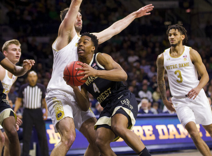 Wake Forest's Jahcobi Neath (4) moves by Notre Dame's John Mooney during the first half of an NCAA college basketball game Wednesday, Jan. 29, 2020, in South Bend, Ind. (AP Photo/Robert Franklin)