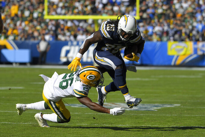 Los Angeles Chargers running back Melvin Gordon runs over Green Bay Packers defensive back Darnell Savage during the first half of an NFL football game Sunday, Nov. 3, 2019, in Carson, Calif. (AP Photo/Mark J. Terrill)