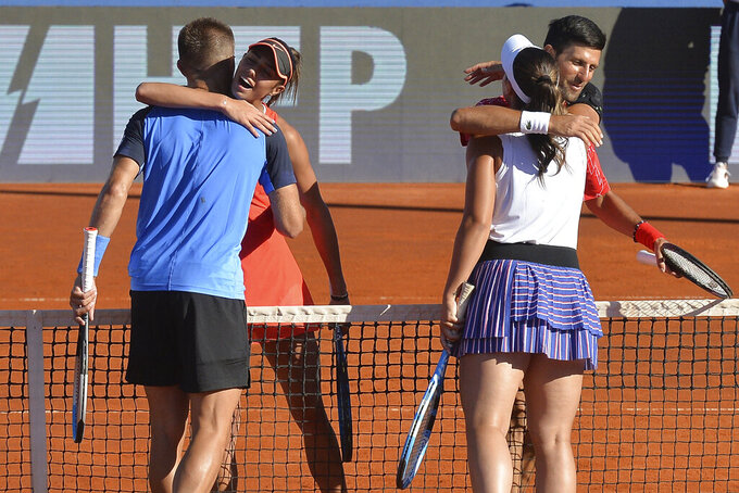 In this photo taken June 19, 2020, Serbian tennis player Novak Djokovic embraces Croatian player Ana Konjuh, right, as Croatian Borna Coric embraces Serbia's Olga Danilovic, during their mixed doubles match at a tournament in Zadar, Croatia. Novak Djokovic has tested positive for the coronavirus after taking part in a tennis exhibition series he organized in Serbia and Croatia. (AP Photo/Zvonko Kucelin)