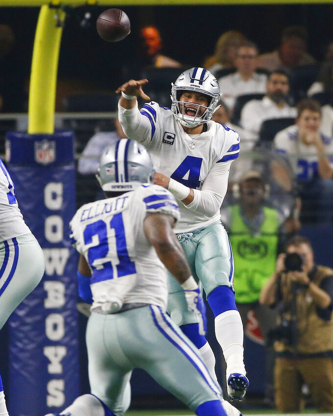 Dallas Cowboys quarterback Dak Prescott (4) throws a pass to running back Ezekiel Elliott (21) in the first half of the NFC wild-card NFL football game against the Seattle Seahawks, in Arlington, Texas, Saturday, Jan. 5, 2019. (AP Photo/Ron Jenkins)