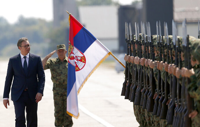 FILE - In this Tuesday, Aug. 21, 2018 file photo, Serbian President Aleksandar Vucic, left, reviews an honor guard on the tarmac at Batajnica, military airport near Belgrade, Serbia. Serbia is considering buying a modern Chinese air defense missile system, the Serbian president said Tuesday, Aug. 11, 2020 despite a warning by the United States that such deals with Beijing could jeopardize the Balkan country's proclaimed European Union membership goals. Serbian president Aleksandar Vucic said that