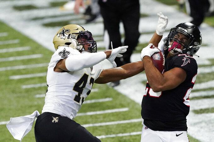 New Orleans Saints cornerback Marshon Lattimore (23) hits Atlanta Falcons running back Brian Hill (23) during the first half of an NFL football game, Sunday, Dec. 6, 2020, in Atlanta. (AP Photo/John Bazemore)