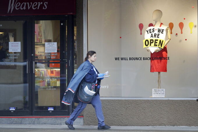 A letter carrier walks past an open department store in downtown Lawrence, Kan., Thursday, April 16, 2020. (AP Photo/Orlin Wagner)