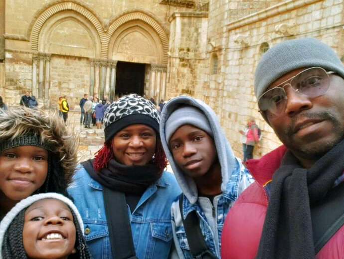 This photo shows the Brown family of Atlanta, from left, Jayde Brown, Jay'Elle Brown, Jayson R. Brown, Tammy Brown and Jayson E. Brown at the Church of the Holy Sepulchre in Jerusalem on Dec. 27, 2019.  Parents Tammy and Jayson have been taking their kids on educational trips for five years and are among families heading out with remote-learning kids during the new school year rather than leaving them stuck at home. (Jayson E. Brown via AP).