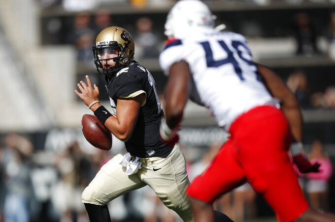 Colorado quarterback Steven Montez, back, scrambles out of the pocket to avoid Arizona defensive end Jalen Harris in the first half of an NCAA college football game Saturday, Oct. 5, 2019, in Boulder, Colo. (AP Photo/David Zalubowski)